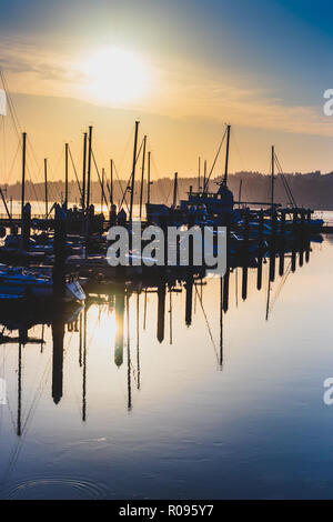 Morning sunrise harbor with hazy filtered light and shadows - Stock Photo