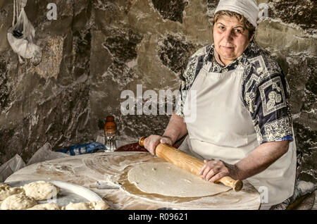 Ashtarak,Armenia,19 Februar,2018: Armenian woman rolls out the dough a wooden rolling pin into very thin sheets for the traditional lavash bread in th - Stock Photo