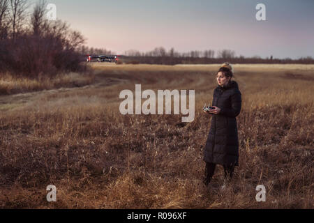 Female drone pilot looks at drone while operating in a field during autumn at dusk. - Stock Photo