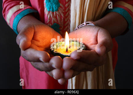A girl holding isolated lit diya to celebrate diwali and dhanteras - Stock Photo