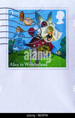 Alice in Wonderland 2nd class postage stamp stuck on envelope and franked - Stock Photo