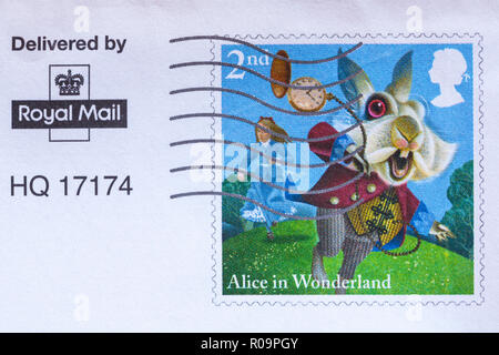 Alice in Wonderland 2nd class postage stamp stuck on envelope and franked - delivered by Royal Mail - Stock Photo