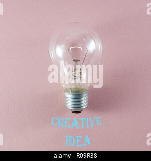 Creative idea and innovation concept via lit bulb on pink background and relevant text in modern font - Stock Photo