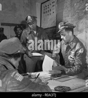 Tuskegee Airmen attending Briefing at Air Base, Woodrow W. Crockett, standing at center, Edward C. Gleed, Lawrence, KS, Class 42-K, Group Operations Officer, Seated on Right, and Unidentified Airman Seated on Left, Ramitelli, Italy, Toni Frissell, March 1945