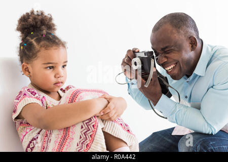 Young father with his cute little daughter taking pictures of each other on an old vintage camera - Stock Photo