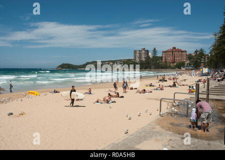 View along the golden sands of Manly Beach, Sydney, Australia with holidaymakers sunbathing, swimming and surfing in the spring sunshine. - Stock Photo