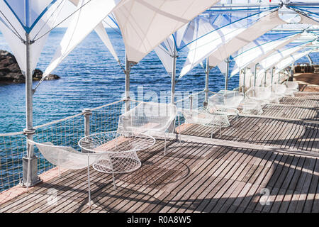 Сafe with white tables in front of the sea - Stock Photo