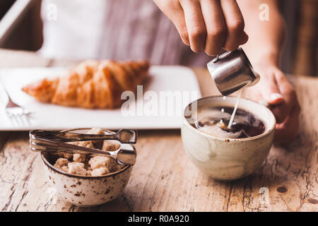 Woman hand pouring milk in coffee - Stock Photo