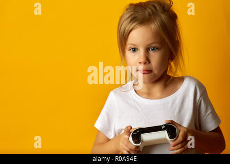 Little absorbed girl in white t-shirt holding game pad playing video game on yellow background - Stock Photo
