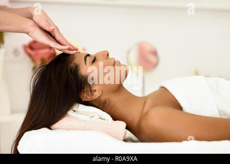 Arab woman receiving head massage in spa wellness center. Beauty and Aesthetic concepts. - Stock Photo