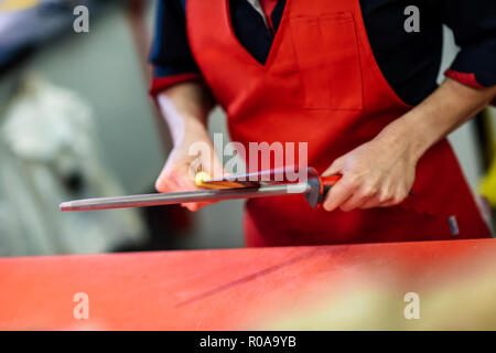 Young female butcher sharpening a knife in a butcher shop - Stock Photo