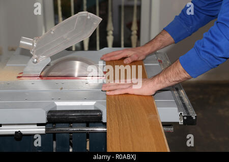 Worker laying parquet flooring. A worker saws off the floorboard - Stock Photo