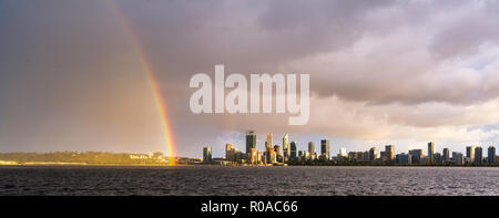 A rainbow over Perth city and the Swan River at sunrise. - Stock Photo