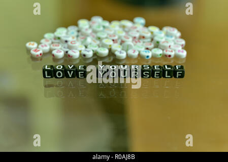 LOVE YOURSELF  written with Acrylic Black cube with white Alphabet Beads on the Glass Background - Stock Photo