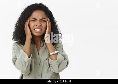 Head goes round from hangover. Portrait of displeased intense african american young woman with curly hair frowning clenching teeth from painful feeling touching temples suffering headache or migraine - Stock Photo