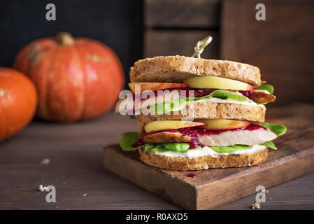 Turkey or Chicken Leftover Sandwich with stuffing and cranberry sauce. Freshly made from Thanksgiving or Christmas turkey leftovers on crusty wholemea - Stock Photo
