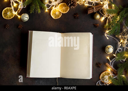 Christmas background with vintage blank open book, decor, lights and fir branches around on dark table, top view. Layout with empty copy space for tex - Stock Photo
