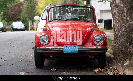 A vintage red Volkswagen beetle parked up in a side street. its a car in excellent condition bearing American number plates - Stock Photo