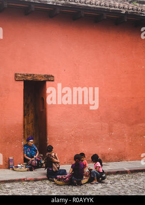 Matriarch of Guatemalan family in traditional Mayan dress sells jewellery & cloths from baskets on the street next to her family in Antigua Guatemala - Stock Photo