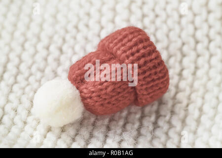 Little knitted decorative red beanie with pompon on a knitted sweater - Stock Photo