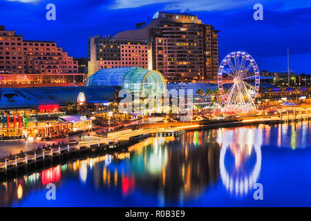 Ferries wheel on waterfront of Sydney Darling Harbour and harbourside entertainment area with boardwalks, cafes, hotels and accommodation at sunset wi - Stock Photo