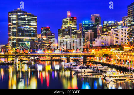 Waterfront of Sydney city CBD high-rise towers around Darling harbour with marina boats over Pyrmont bridge reflecting in still waters at sunset. - Stock Photo