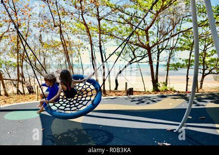 Two children playing on a nest swing, Balgal beach, QLD, Australia