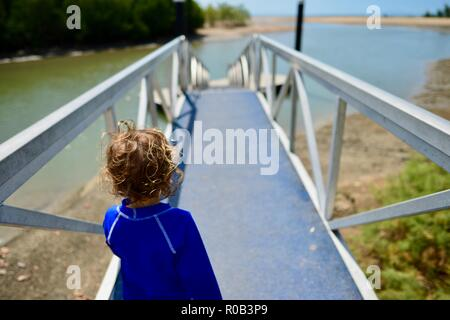 Child walking down to a floating pontoon at the mouth of a tropical river, Balgal beach, QLD, Australia - Stock Photo