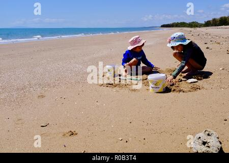 Children playing in the sand with buckets and spades, Balgal beach, QLD, Australia - Stock Photo