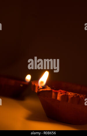 Closeup of Diwali terracotta diyas on dark background which are used lighting up the house during diwali times - Stock Photo