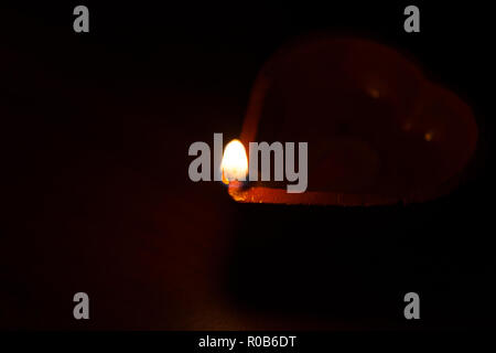 Closeup of Diwali terracotta diyas on a dark background which are used lighting up the house during Diwali times - Stock Photo