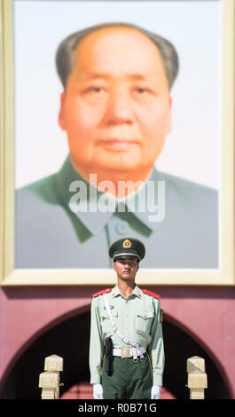 A Chinese soldier standing in front of Mao Zedong's portrait - Stock Photo