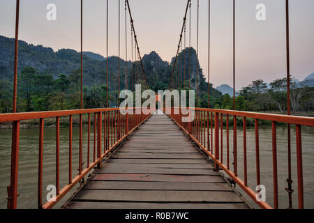 Suspension footbridge over Nam Song River and scenic limestone mountains near the Tham Chang (or Jang or Jung) Cave in Vang Vieng, Laos, at sunset. - Stock Photo