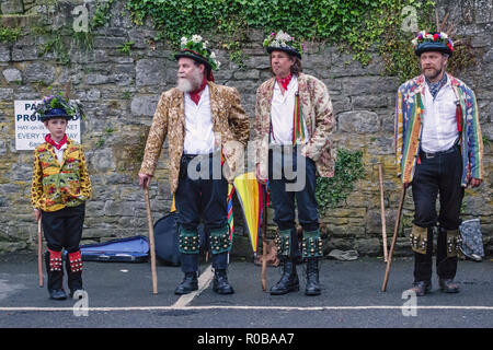 Hay-on-Wye, Powys, Wales, UK. Morris dancers (3 men and a young boy)  in traditional costume waiting to dance in the town square - Stock Photo