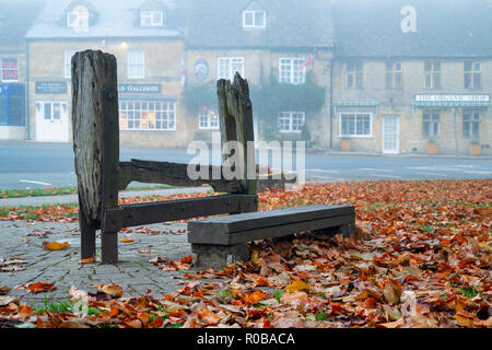 The village penal stocks on the green in the early morning autumn fog, Stow on the Wold, Gloucestershire, Cotswolds, England - Stock Photo