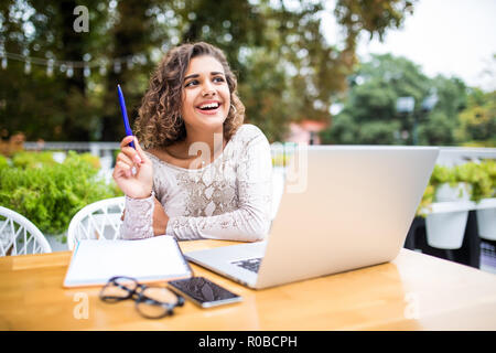 Photo of young excited latin curly woman indoors using laptop computer writing notes Looking aside have an idea. - Stock Photo