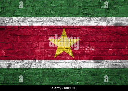 Flag of Suriname over an old brick wall background, surface - Stock Photo