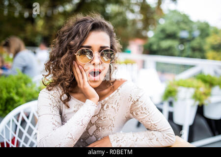 Portrait of shocked and surprised stylish woman in cafe with amazed and afraid expression - Stock Photo