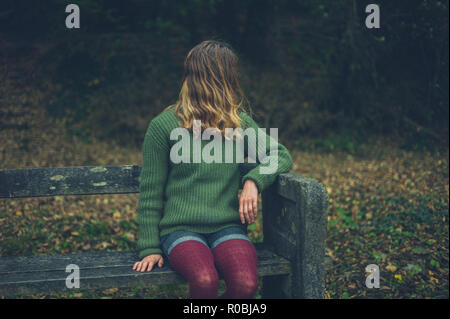 A young woman is sitting on a bench in the woods in autumn - Stock Photo