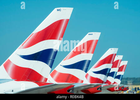 British Airways tailfins showing the company logo on aeroplanes parked in London Heathrow - Stock Photo