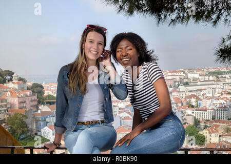 Two young female friends - one African, one European, sitting on a wall on a summer's day with the skyline of Lisbon behind them - Stock Photo