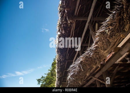 Typical straw roof of traditional wooden house in rural Guatemala against a vibrant blue sky - Stock Photo