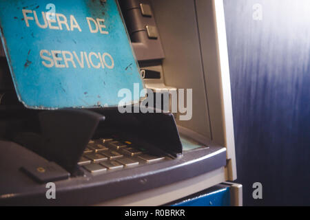 Pin keypad of ATM cash withdrawal machine with a sign that reads 'out of service' in Spanish - Stock Photo