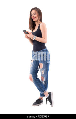 Young carefree happy woman holding smart phone smiling and looking away in trendy jeans. Full body isolated on white background. - Stock Photo