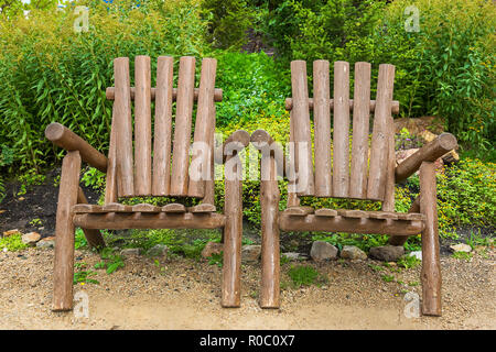 Wooden chairs made of rough wood trunks for relaxing in a park on the nature - Stock Photo