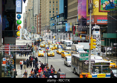 NEW YORK - MARCH 16, 2015: Yellow taxi cabs and people rushing on Times Square, downtown Manhattan. Taxicabs with their distinctive yellow paint are a - Stock Photo