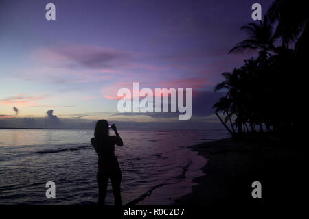 Silhouette of solo female backpacker takes a photo of a sunset using her phone on a paradise beach in Central America - Stock Photo