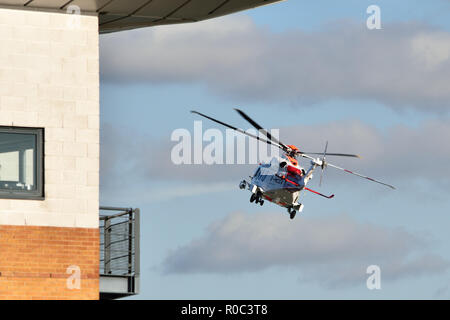 Coastguard rescue helicopter taking part in a search and rescue mission over the river Thames in East London - Stock Photo