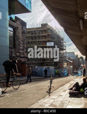 GLASGOW, SCOTLAND - NOVEMBER 2nd 2018: A students going to class while workers work on the site of Glasgow School of Art. - Stock Photo
