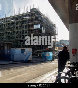 GLASGOW, SCOTLAND - NOVEMBER 2nd 2018: A man leans on a wall while workers work on the site of Glasgow School of Art. - Stock Photo